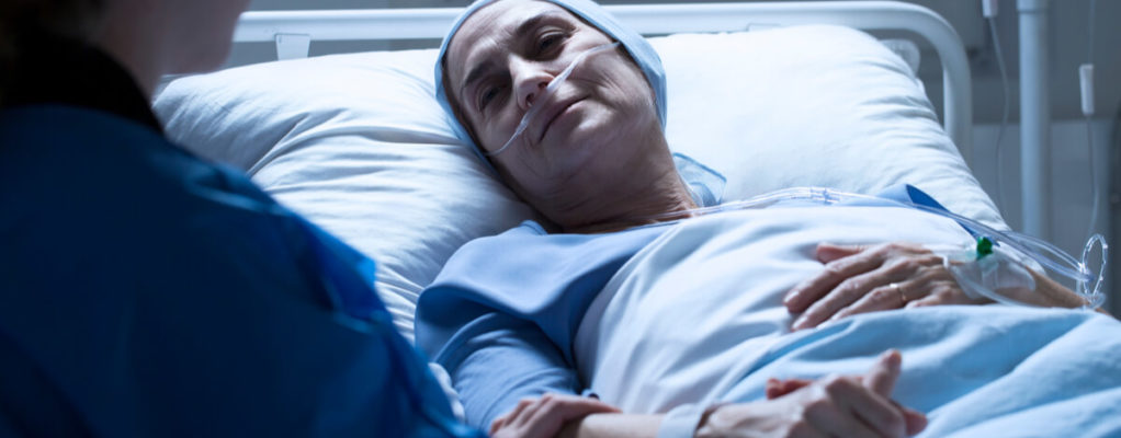 a woman lies in a hospital bed while receiving cancer treatment