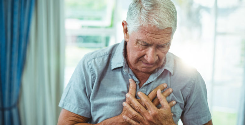 an older man holds his chest in pain