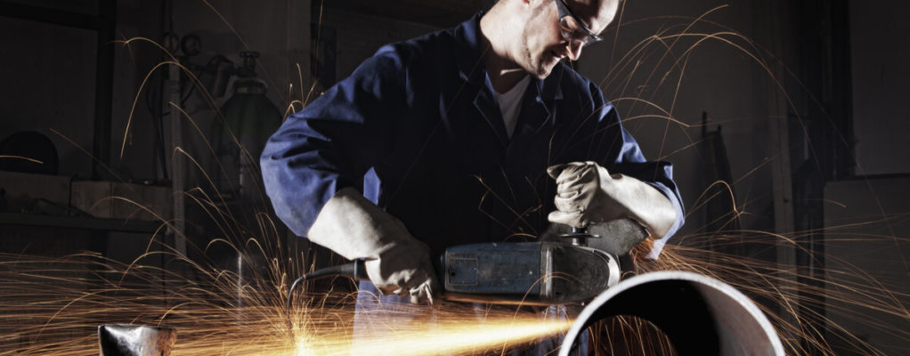industrial worker in a workshop with sparks and dust in the air around him